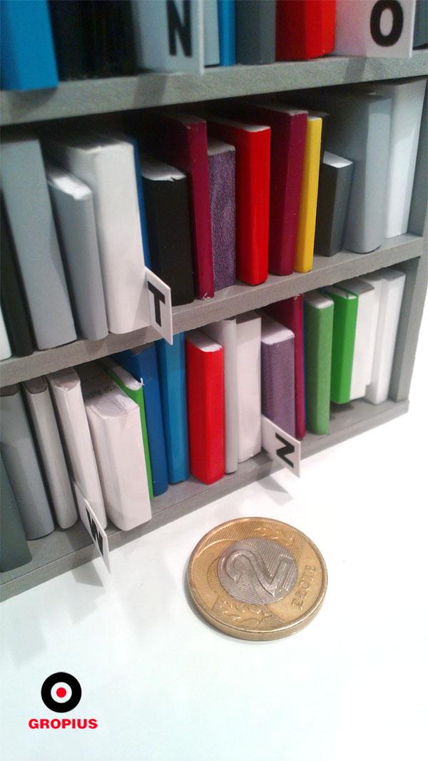 Regał biblioteczny mieści miniaturowy księgozbiór